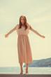 Woman dancing wearing long light pink dress