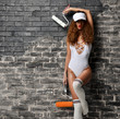 young female construction worker butt glamour sexy young woman wearing white body with building paint roller tools