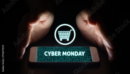 Man hands holding smart phone with cyber monday text and cart on virtual screens on smartphone.