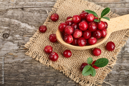 Poster Cranberry with leaf in spoon on old wooden background
