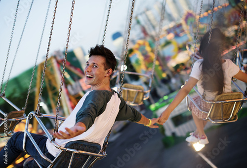 In de dag Amusementspark Young couple riding the swings at an amusement park