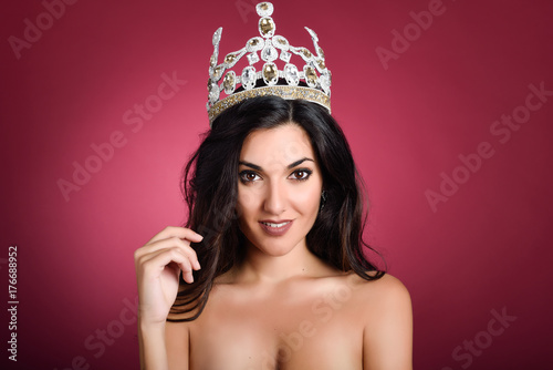 Crowned woman like miss of beauty looking at camera
