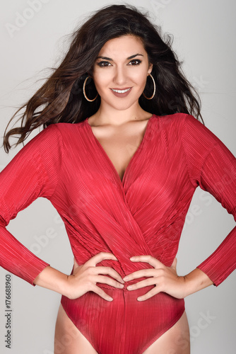 Young woman wearing red body and earrings on white background.