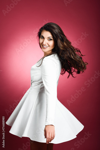 Young woman wearing short white dress smiling to camera.