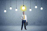 Businessman standing uninspired with bulbs above - 176689144