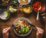 Eating healthy vegetarian meal in bowl with chick peas puree, roasted vegetables , red paprika tomatoes stew, avocado and seeds . Clean or dieting, vegetarian food concept - 176690777