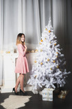 A beautiful woman in a dress decorates a Christmas tree. A beautifully decorated room with a fireplace and a Christmas tree for Christmas and a New Year in white. Winter card.