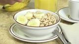 Slicing a banana onto a bowl of cold cereal - 176697764