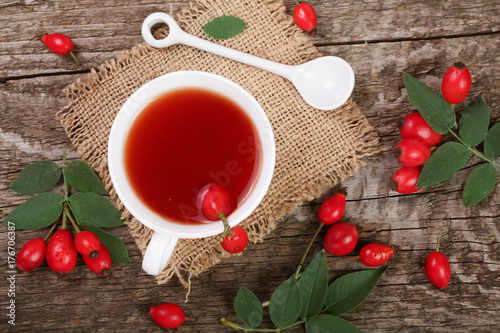 tea with rose hips on old wooden background. Top view