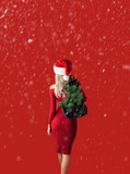 girl in a red dress on a red background in a santa hat with a backpack out of which the branches of a New Year tree stick out