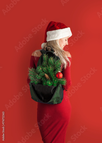 Plakát girl in a red dress on a red background in a santa hat with a backpack out of wh