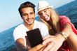 Beautiful young couple using mobile phone on the beach.