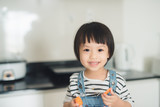 Child girl having fun with carrot. Home kitchen interior with fruits and vegetables. - 176713505
