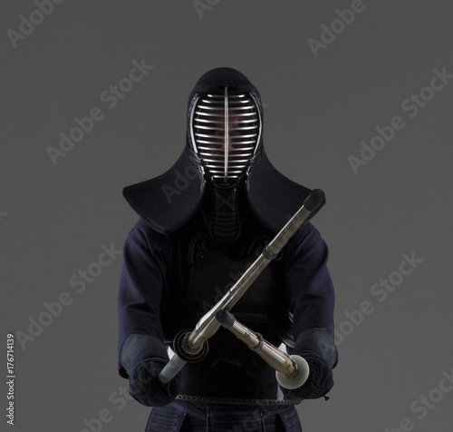 Portrait of man kendo fighter with two bamboo swords in traditional uniform Poster