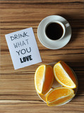 A cup of coffee and orange on plate on wooden zebrano background. Inscription drink what you love - 176722594