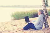 ältere Frau am Strand mit Laptop - 176722997