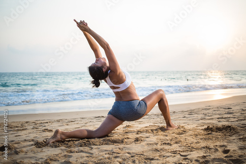 Plakat Natural looking pregnant woman practicing yoga at the seashore at sunset