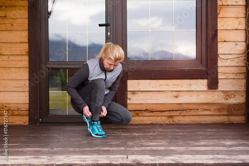 Sport runner woman tying laces before training. Marathon.