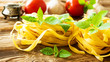 Raw tagliatelle pasta with fresh basil, garlic and tomatoes on rustic wooden table