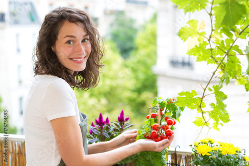Fridge magnet Young woman taking care of her plants and vegetables on her city balcony garden - Environment and ecology theme