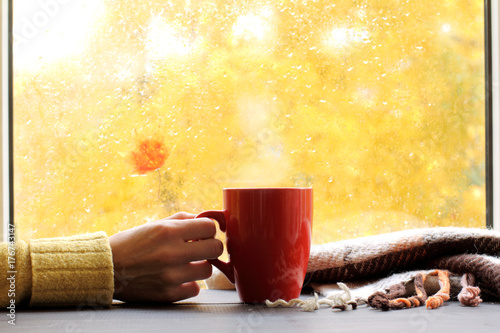 Papiers peints Cafe golden time for rest/ red mug of hot drink, when behind a window is rain in autumn