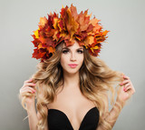 Beautiful Young Woman with Autumn Leaves Touching her Hand her Hair. Fashion Model with Makeup, Blonde Curly Hair and Fall Wreath - 176745108