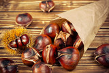 chestnuts in paper bag on wooden background - 176764147
