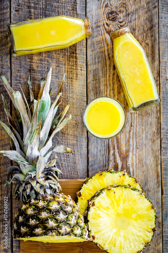 Fotobehang Sap Freshly squeezed pineapple juice near fruit slices on wooden background top view