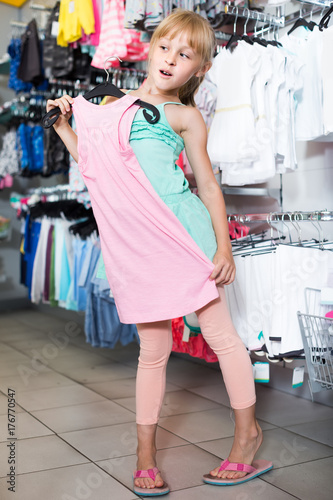 Plakát Portrait of girl choosing colored dress and wear in the shop