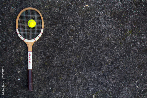 Plakat Old vintage wooden tennis racket on isolated stone background with green ball