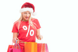 happy young woman with santa hat carrying shopping bags - 176772504