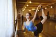 young cute ballerina holding rack in ballet class