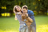 Lifestyle, happy couple of two walk on a sunny day in the park with a dog - 176778788