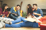 Happy young friends having fun at home listening vintage vinyl disc music in living room - Group of people enjoying their time in apartment drinking shots and laughing - 176785934