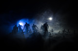 Silhouette of zombies walking over cemetery in night. Horror Halloween concept of group of zombies at night - 176786122