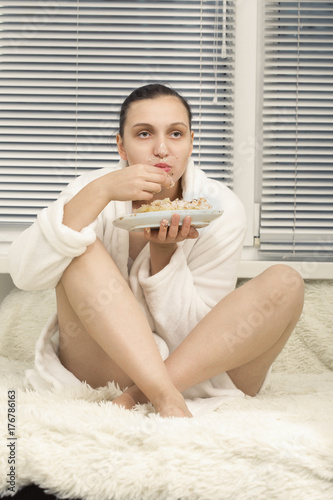 hungry sad young woman in bathrobe with sweet biscuit cake sitting on bed