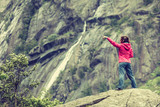 Woman on mountain rock enjoying beautiful view