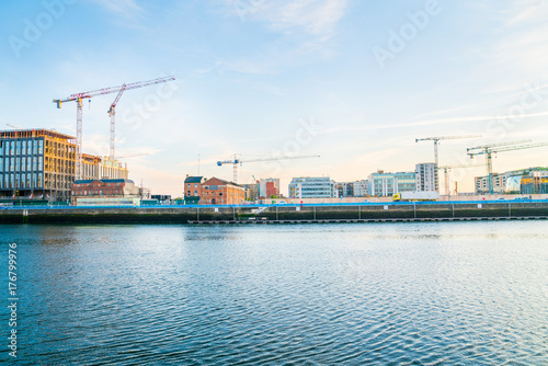 Dublin building boom illustrated inearly morning image across Liffey River an array of old wharf, modern newer, and underconstruction buildings with constructuction cranes across skyline Poster