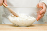 Chef's hands with wooden spoon stirring a cottage cheese in the glass bowl for making pie, cake, sweet dessert or pancakes in the kitchen. Preparation for cooking. Food concept. - 176806157