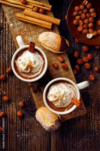 Papiers peints Cafe Hot chocolate with whipped cream sprinkled with aromatic cinnamon in cups on a wooden table, top view. Delicious and warming drink.