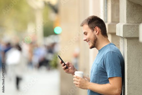 Side view of a man using a smart phone on the street
