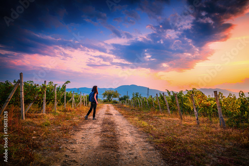Fotobehang Diepbruine Young girl with a backpack in Bulgarian vineyards on a Sunset ready to travel