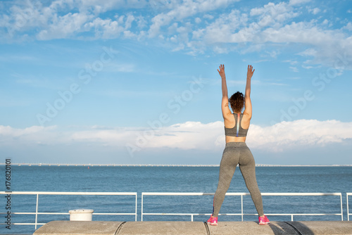 Sporty Girl Exercising on Parapet by River Poster