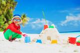 little boy building sand castle on beach
