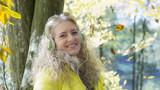 Frau im herbst mit Kopfhörer im Park. - 176838967