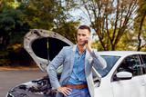 Young man stands next to a broken car calling - 176839130