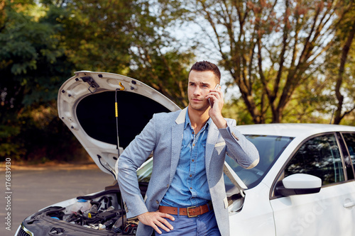 Wall mural Young man stands next to a broken car calling