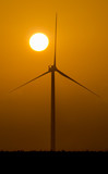 Silhouette of an isolated wind turbine at sunset with foggy and misty weather - 176840300
