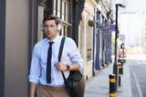 Businessman Wearing Wireless Headphones Walking To Work - 176842164