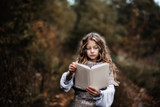 Beautiful little girl with curls, reading a book in a dark and scary forest. - 176842366